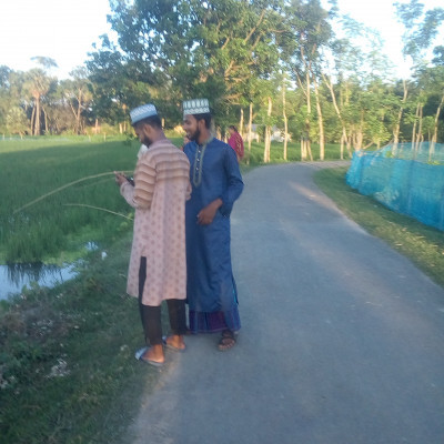 This picture is of two of my friends.  Those who work on the release.  They are both members of the release.  Those who are standing here.  They are standing on the side of a road.  Where some people are seen fishing.  They are fishing with fishing rods. A paddy field can be seen here.  It is now full of water.  So there have been lots of fish here.  Different people come here to fish. There are also beautiful trees along its banks.  All in all this place is very beautiful.  We take occasional walks along the road here. One day the three of us went for a walk and took this picture.
