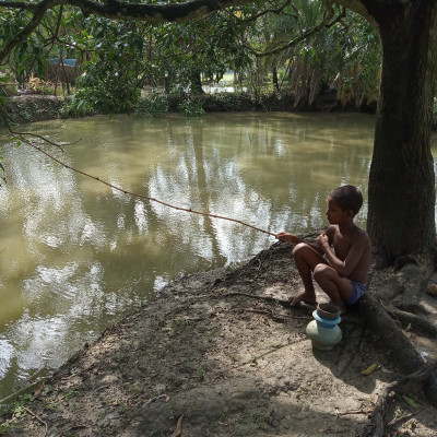 A beautiful view of a small village boy fishing in a pond with a rod.