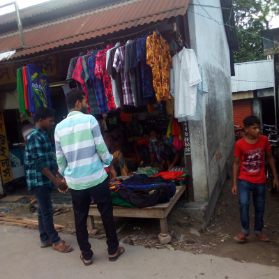 This is the picture that is seen here. There are different types of clothes and buyers are coming to buy them.  This photo was taken from Dhulihar Bazar, District Satkhira, Bangladesh.  There are people in this store to buy them.  People are flocking to this shop because they need clothes now.  So they are coming to buy clothes.  These people do not go to any store without their need.  They come to the market with exactly what they need to buy.  And the shopkeepers in the market are always waiting for the buyer to come and buy some of his things.  People continue their daily work in this way.  It benefits a lot of people who go to the market every day to buy clothes and other things. A lot of people work hard and want to live happily in peace. There are many kinds of clothes in this shop and these are for sale by shopkeepers.  Left.