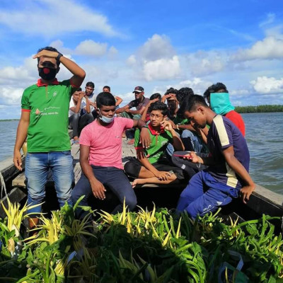 The picture shows some boys coming together in a boat.  They are all wearing the same color vest.  Some food packets can be seen in front of them.  They have different types of raw vegetables in this food packet.  Usually this year due to flood waters, relief materials have been taken to the coastal areas of Satkhira and these relief materials will be delivered to every house.  They are getting on the boat in a very beautiful way by arranging these in the boat.  The scene of them bringing them is very beautiful. They are taking them because of the floods in the coastal areas of Satkhira district. People are not getting food there because all the houses are submerged due to the floods.  That's why these boys are carrying relief materials for them.  The sight of them carrying relief supplies in their boats looks very beautiful. They have brought these food items from far and wide and they will give a packet of food to every house and they will distribute these food items among the flood-affected people.  The scene of bringing these foods by boat.
