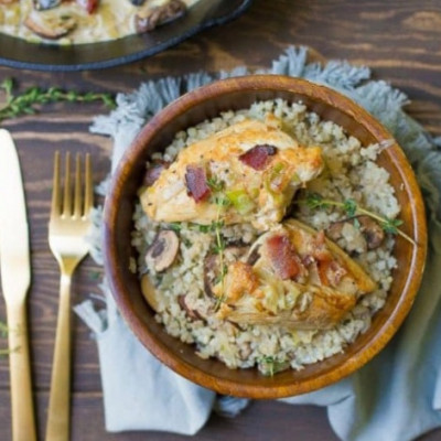 "This is the ultimate comfort food healthy dish!! A creamy mushroom sauce with skillet chicken, crispy bacon, and plated on top a Cauliflower Rice Mushroom Risotto. This recipe can be made fast for a healthy weeknight meal, but also is elegant enough to serve to guests!OMGEEEEEE. You guys are going to love this dish! I finally took one of my personal favorite dinners and reader favorites, Creamy Maple Dijon Chicken with Bacon, and made it into a Whole30 friendly dinner.  My goodness…. it is pure perfection.  Bacon is cooked to crisp, followed by pan seared chicken, then the addition of mushrooms and leeks. Just like the original recipe, the creamy portion comes from full fat coconut milk (no coconut taste), and dijon mustard. I then served on top a bed of cauliflower rice ""risotto""."
