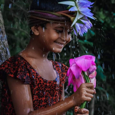 If we can see in this picture is a little girl.  This little girl is seen getting wet in the rain.  This girl has picked water lilies from the village river or from the canal-bill.  Two shopaholics are seen tied to the head which looks very beautiful and extraordinary.  It is a very common flower in our country. It is the national flower of Bangladesh. It looks soaking wet in the rain. It looks very amazing to see these flowers.  The children have picked up water lilies from the village field, some of them are sold, some of them are cooked and eaten at home and this little girl is seen picking flowers and tying them on her head which looks very amazing to her.  Such a scene came to light in the village.