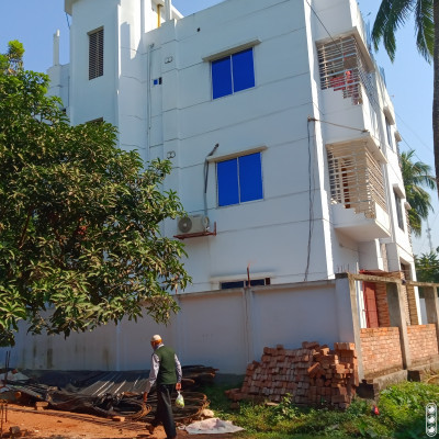 Here you see a picture of a building and a man walking next to the building.   He is going down this road to reach his home.  And next to it you can see there is a mango tree.   And that's when the mango tree.  Then this tree is mango.  Much more and I like to eat these mangoes.  Is nutrition.   There are trees that meet all the needs.  I talked about this.  And the building looks very beautiful.   The way it is made is very good.  The two-storey building looks very beautiful all around.   The white color of the building has become attractive.  It has become more attractive from afar.