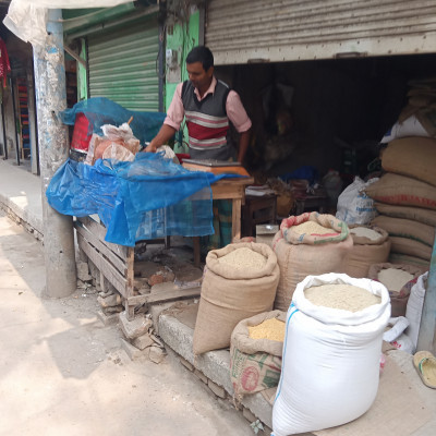 In the picture here we can see a rice shop.  This shop is located in Munshiganj Bazar of our Satkhira district.  Here on the road they can see the view of the shop.  It is located on the side of the road.  This shopkeeper is a rice trader.  He has been in the rice business for a long time.  We can see that there are different arrangements of his shop in front of the shop.  This is a beautiful view.  We can see that there are sacks of rice in front of the shop.  And this rice is the main food of the people of Bangladesh.  Everybody in Bangladesh cooks rice for help.  That is why there is a greater demand for rice than us.  He made money by selling that shop.  He keeps the store open every day.  And by trading this rice he is known to all as an established trader in the market.  Here in the picture you can see the rice in front of the shop.