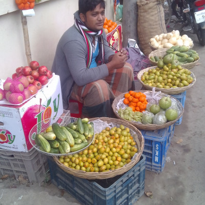 The picture shows a man selling a variety of fruits in a basket.  In the picture we see a man sitting on the side of the road selling a variety of fruits such as cauliflower, guava, apple, sugar potato, orange, pomegranate, cucumber and many more which are very nice to look at.  In fact, the people of Bangladesh like to eat such fruits. The picture is taken from our market, which is why the picture looks so beautiful.  I find it very nice to see the fruits in the fruit shop.  I hope you enjoy the fruit shop.  Honestly, it is very good to eat such fruits. The man is selling very good fruits which look very nice.  I hope the picture looks very beautiful.