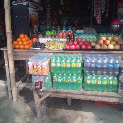 The picture shows a fruit shop.  Here you can see a variety of fruits being sold which look very nice.  Here we can see some drinks being sold along with fruits.  Such as Clemon, Tiger, Speed, Cumin water, Mojo and many more types of drinks that look very good.  Moreover, the people of Bangladesh like to drink such drinks.  Such drinks are made from more and more companies in Bangladesh because such drinks are very popular among the people of Bangladesh.  The picture is taken from our Dhulihar market which is why the picture looks so beautiful.  We can see in the picture that different kinds of fruits are being sold here like apples, oranges, pomegranates, grapes and many more kinds of fruits which are very good to eat.  I find it very nice to see the fruit shop.  Hope you enjoy the fruit shop.