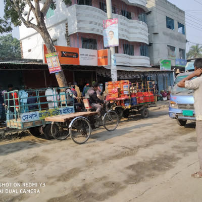 Good afternoon friends, how are you all? I have posted a picture of the landscape of a new market and the old Satkhira Munshipara Bazaar where this market is located and the picture shows a beautiful road and two engine vans and vans on the left side of the road with many gas cylinders arranged.  And there's a guy sitting on the first van and there are two guys standing on either side of him and there's a nice drain on the left side of the road and there's a lot of shops on the side of the drain and there's a shop full of flour so there are a lot of people standing in rows.  On the drain and on the ground in front of them everyone has a packet in front of them and a big mahogany tree can be seen in front of them and a bike can be seen under the tree and charger van easybike motorcycle bike etc. is moving on the road and by the road  A lot of people are walking and there are two big buildings and the shops are tented with tin and on the right side of the road.  The buildings can be seen, and the buildings are of all kinds, small and large, and of different colors, and in one building, there are two electric poles in the front, and on the poles, there are many electrical electronics, and there are many different types of plants on the sides and in the back of the buildings.