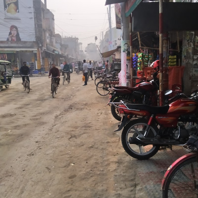 Good evening friends, I posted a picture of a beautiful market landscape among you and this market scene is adjacent to Satkhira Munshipara College Junction Road and the picture shows a beautiful road and a beautiful food hotel on the left side of the road and three people are standing inside the hotel and  A few bikes are seen behind them and a few motorcycles are seen on the street in front of the hotel and a man is sitting on the bikes on the street next to it and a nice food shop is seen on the west side of the hotel and a lot of food is hanging in front of that shop and next to it.  A gas cylinder shop can be seen and there are many gas cylinders arranged and a few women are walking along the street in front of that shop and the shops are under a building and a few shops on the right side of the street and the shops are tinned.  And a lot of vans, bicycles, motorbikes, etc. are moving along the road and from this road on the right side of the road  A beautiful road has gone through the ash and there are many small and big buildings on both sides of the road