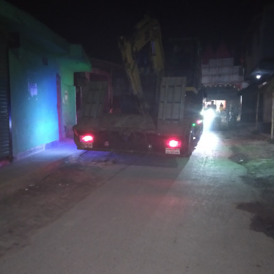 This picture shows a beautiful road building machine or car and with this car the road is broken or the building is rebuilt and this car is located at our house in Dhulihar Bazaar at the turn of Saheb Bari and this car is standing on a pitch road and the car is seen in front.  There are two red lights on either side and a few lights on the right side of the car and a few buildings on either side of the car and a cloth Degart gate in the back of the car and a charger van with a few people on the left side of the car.  Coming and so on