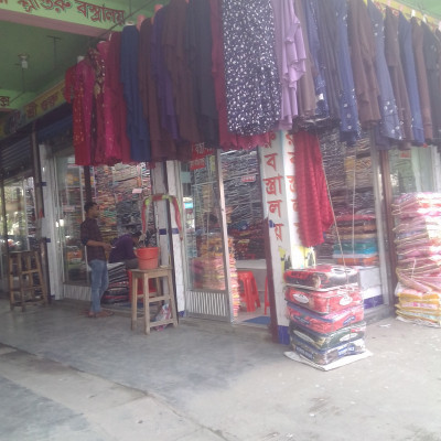 Shri Guru Vastralaya.  In the picture you can see Sri Guru Bastralaya. Here you can see different types of clothes being sold.  Here you can see the girls burqa, hijab, sari, thripich and many more types of clothes.  Moreover, all kinds of food pants, shirts, Punjabi and many other types of clothes for boys.  It can be called a big clothing store. The picture was taken from our Budhahata market which is why it is very nice to see the picture. The demand for clothes is high in Bangladesh.  I like to see the clothes of Guru Bastralaya very much.  I hope you and I are very happy to see the clothes of Glass Guru Bastralaya.  In fact, people in our area buy a variety of clothes from here.  I hope it is very good to see the picture. Honestly, it is a very big and good clothes shop in Satkhira district.