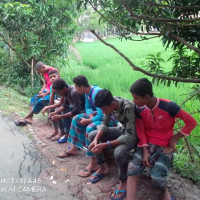 Here you can see a lot of boys sitting together and these are the boys from rural areas. This scene looks very beautiful. Every boy in our Bangladesh loves to live in such a beautiful way and then it is seen that many boys are sitting here playing games. The name of this game is Free Fire game.  Since then most of our boys in Bangladesh have been playing this game and they have become very addicted to this game and because they are addicted they play this game all day long and because each of them has no work they are spending their time like this and look very nice.  This is a scene from our Bangladeshi rural area. The boys in the rural area love each other very much and depend on each other. Because they love each other, they help each other in times of danger and they extend a helping hand.  Living and looking very beautiful is a very beautiful scene of our rural boys in Bangladesh starting from this morning  They sit here from noon till noon and from noon to many nights they sit here and play different kinds of sports in different ways and it looks very nice it is a feature of our Bangladeshi rural boys and they sit inside the beautiful nature and it is seen that they match  Mishe is sitting very nicely.