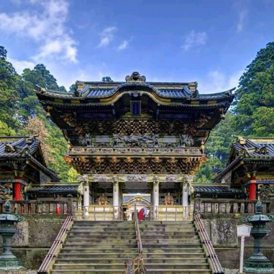 This is a picture of a temple. It is located in Japan.  Everyone should be fascinated by its aesthetic craftsmanship. The temple is a sacred place. Everyone gathers here in the hope of virtue. They will be freed from sin and purify the mind. It is such a beautiful picture.  Made with artistic attitude.  It deserves true praise in terms of its structure. The place where the temple is built is surrounded by green palms. It is like a symbol of religious peace in the middle of a green. There is a beautiful staircase to climb the temple. There are railings in between. I am fascinated by the artistic form of this temple again and again.  This is a beautiful temple built in a beautiful environment.