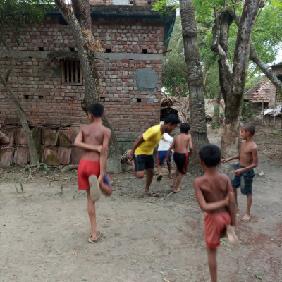 Little boys in the village play cock fight.