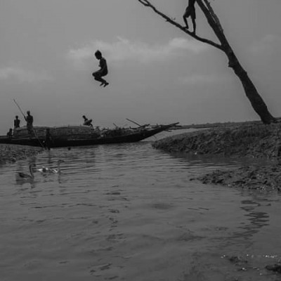 The picture seen here is taken from a river in Kashimari area of ​​Asashuni upazila of Satkhira district of Bangladesh. This picture was taken at a time when the river was flooded with tidal waters and many boats were sailing on the river and a tall tree beside the river was where the boys were jumping into the water. The boys of the village play in this river all the time and they come here and spend time and they swim here by fishing and have a lot of fun. So it is a natural beauty of rural Bengal, it is very amazing to see, So the fishermen fish in this river and they sell that fish in the market which deprives their family of financial prosperity and here they spend time every day and in the river they have a lot of they work hard on the river.