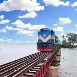 This picture is of a beautiful train.  Which is going through a rail line.  The railway is built on a beautiful river.  It looks so beautiful.  Passengers like to travel in such an environment.  All around is just water and the water is a beautiful railroad over it.  The blue sky in the open sky above it looks so beautiful.  Sounds great.  Besides, it is very beautiful to go over the river to see this sky. The mind is filled with joy.  An island can be seen rising inside this river.  So that there are beautiful trees. All in all, this picture looks beautiful.