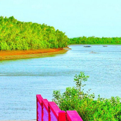 This picture is of a river.  The river looks very big.  There are green trees on both sides of the river.  It is a beautiful landscape.  Such scenes are rarely seen in the world.  It is located in a district of Bangladesh.  Bangladesh has natural beauty.  One of the pictures shows a boat.  Green plants are also seen.  The river is located in Bangladesh.