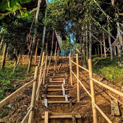 There is a beautiful scene in the picture.  Here you can see the stairs made of bamboo to climb the hill. It looks very beautiful.  Stair method has been made on the mound of soil.  This staircase looks very beautiful. It is made for climbing a small hill in Satkhira.  There are some houses on this hill.  The stairs have been made to get there.