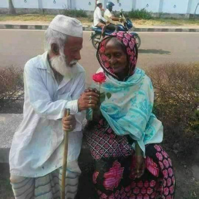 Love is in every human being.  The picture shows a grandfather giving flowers to a grandmother.  Their love is unwavering.  They have been in love since childhood and yet they love each other in old age.  That's why this grandfather is giving roses to his grandmother. They are sitting on the side of a road.  They look so beautiful.