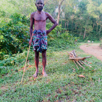 This picture shows a man standing with a stick in his hand. The man's house is in Daodhara village of Nalitabari police station. This guy has a black complexion and a full beard. This picture was taken from Garo hill of Nalitabari police station. The man is standing in his lungi. A small load of straw can be seen beside him.  This man is disabled. He can't talk. But his memory is good. He can understand everything. He is a speech impired. He has many cows. He takes the cows to the mountains every day to eat grass.