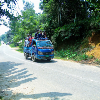 The picture was taken from Daodhara village of Nalitabari police station. The picture shows people filling a small truck. The road is very beautiful as it is a hilly road. The boys in the truck went out for a walk during the Eid holidays. Every year during the Eid holidays, visitors from far and wide come to enjoy the beautiful scenery of the hilly region. The truck has a large sound box. The boys are dancing to the music of the sound box.  The car is moving aimlessly. They will go around all day wherever they want.