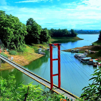 You can see this picture. It is a picture of a natural scene. It looks very beautiful to see this picture.  This photo was taken from the Rangamati hills.  Here you can see there is a hanging bridge.  This bridge looks very nice.  And this bridge has been built over the river.  It is very beautiful to see a river flowing and the water comes in the river and there are many plants beside the river and you can see it looks very beautiful.And we can also see that there are high hills on both sides of this river.  The hills return to the green vegetation.  And we can see that there are many small rocks on both sides of the river.  It looks very nice.  We can also see that the white clouds floating above are amazing beauty.  This picture is surrounded by lush greenery.