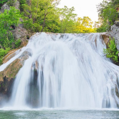 If you are looking for a great camping weekend then Turner Falls, Oklahoma's largest waterfall, is one of the best getaways in the state.Located near Davis, Oklahoma, Turner Falls is a 77-foot-high waterfall, with natural swimming areas surrounding it. This is a perfect weekend getaway for outdoor enthusiasts and families. Besides the main attraction, the massive Turner Falls waterfall, there are caves and other natural areas to explore.You can fish for stocked trout and spend part of your time on the hiking trails making for a full outdoor weekend. The stocked streams in the park are especially popular in the winter.The park around the falls has cabins, camping sites, and an RV park. It is best to book those and the tickets for Turner Falls ahead of time to guarantee your spot. If you have time, make your way south to Lake Murray, which is also a nice outdoor recreation area.