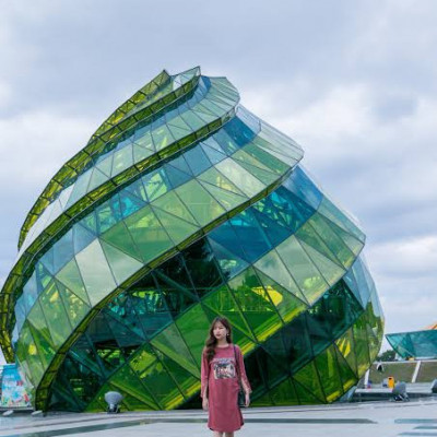 This picture shows a beautiful glass building.  And inside this beautiful environment there is a beautiful girl standing and this girl is seen behind the full grown girl and this girl is made of a beautiful round building city shopping mall and inside it all kinds of clothes and vegetables are found and usually looks like a picture of a city and  There is a beautiful market in the city so that he can be a business owner and this picture looks very beautiful. It is a picture of a beautiful city and this building is surrounded by glass on all four sides and it is located in Japan.