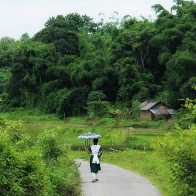 You can see Maligram of Bharukhali Union, a village road in Naogaon district of Bangladesh.  Originally it was gone and the road is now PC road and there are a lot of forested hills surrounded on both sides.  Here, a girl from the countryside, wearing a school dress with an umbrella over her head during the light sun, left for school.At present the weather in Bangladesh is adversely affecting sometimes rain sometimes sun sometimes rain at the same time.  For them, when they go out of the house, you can see this rain and Rudra with an umbrella on his head so that he can resist and save his body.  The green villages on both sides of the road have been made beautiful and the reports have been collected nearby and you can see what looks beautiful here.