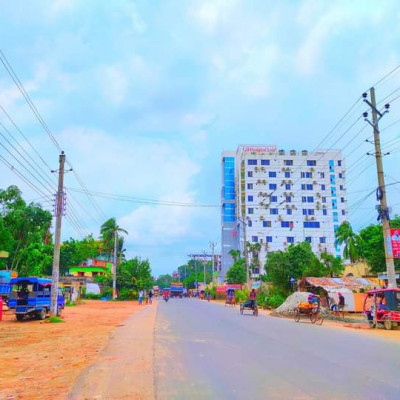 You can see a street picture here. This picture looks very beautiful. This picture was taken from Khulna in Satkhira district.  You can see there are a lot of cars parked on the side of the road.  And we can see that cars are moving on the road, it is very nice to see here.  We can see that there are electricity poles on both sides of the road.  We can also see that there are some tall buildings on the side of the road.  We can see more that there is a huge hospital in front.  This hospital looks very beautiful. The name of this hospital is CB Hospital.  In this picture we can see more trees.