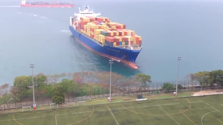Container_ship_sails_straight_to_shore_by_university_football_field.