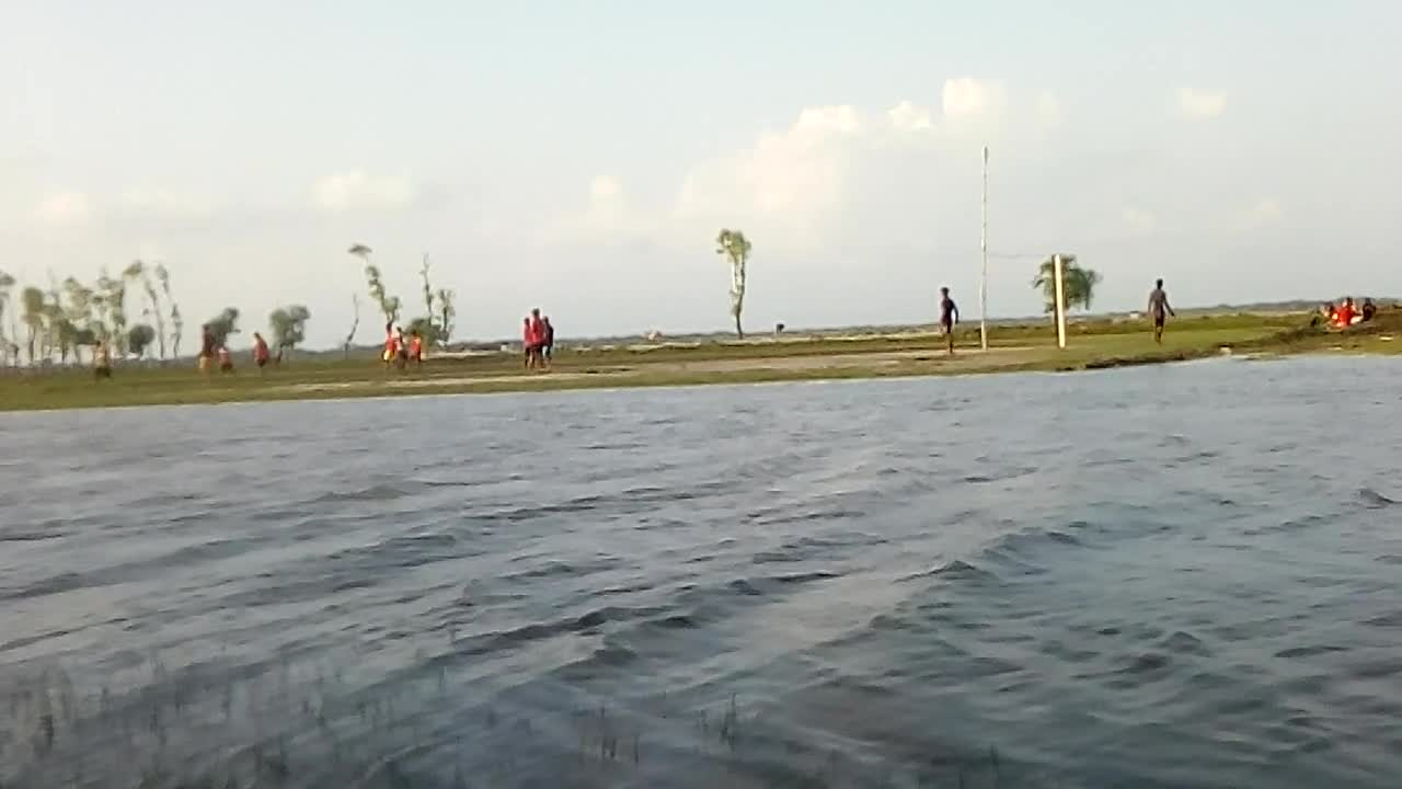 Playing football on the river bank.