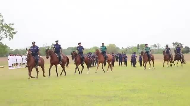 Some policemen are training horses at the police academy