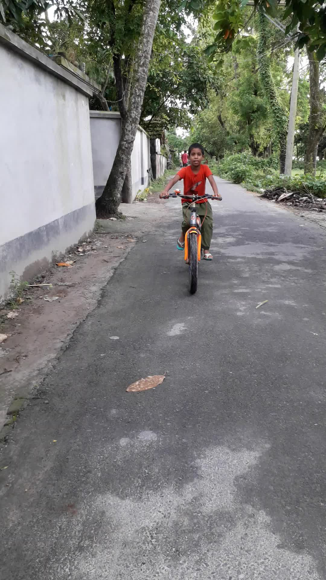 The younger brother is cycling on the street in front of our house in the afternoon,