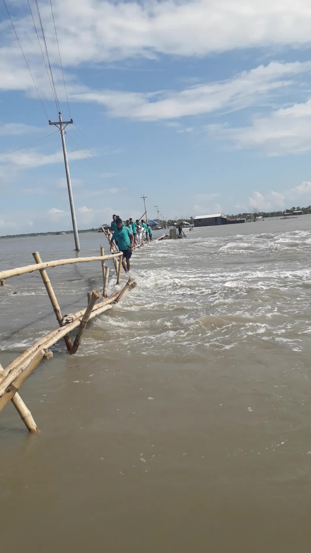 Members of the release are crossing a bamboo bridge over the water at the risk of their lives