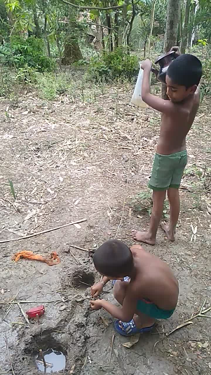 two little boys are playing with water here