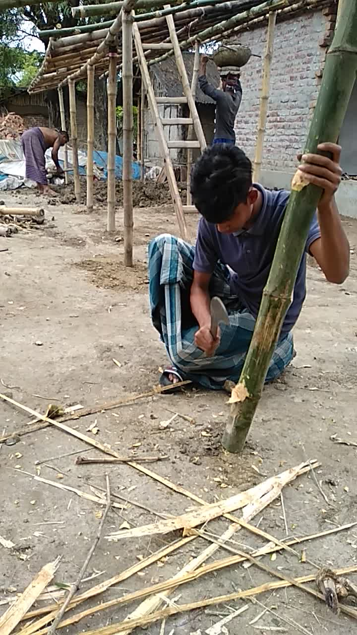video of a boy cutting bamboo to make a shop
