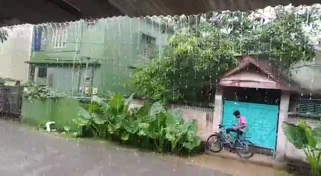 A boy is standing in the rain.
