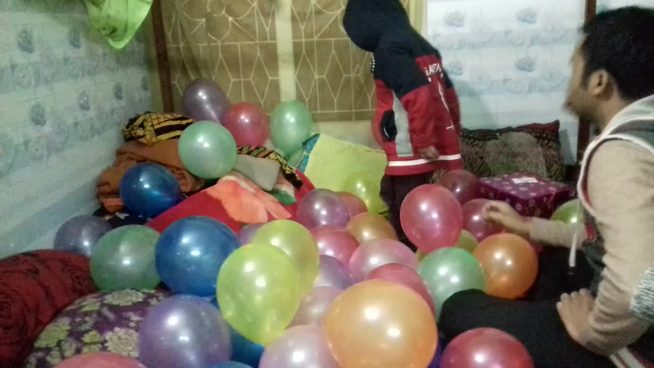 The baby is playing on the bed with the balloons