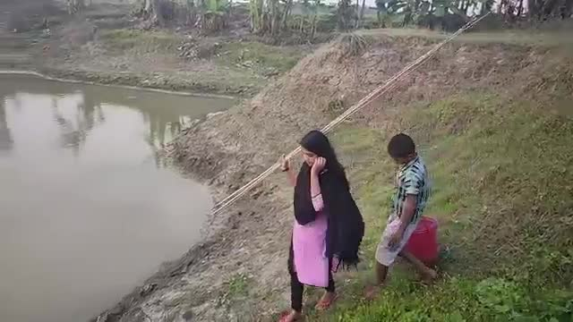 The girl is fishing with a rod while visiting the village house