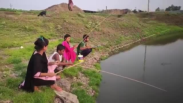 A girl is fishing in the river with a rod