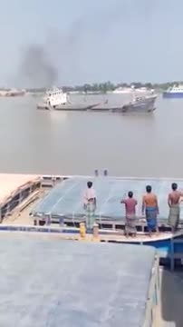 Launch sinking is seen in the river. people standing there watching .