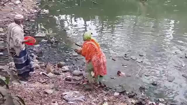 A woman is fishing from the pond