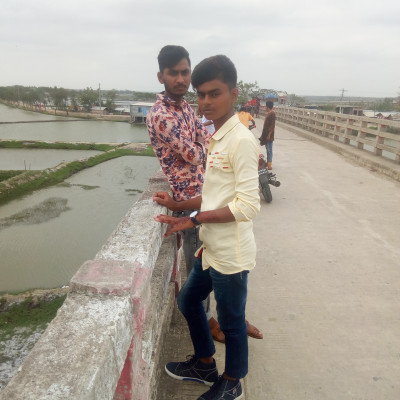 The picture shows two boys standing on a bridge.  They have come to visit on the day of Eid. They are wearing two beautiful clothes.  The picture shows many people coming to the bridge.